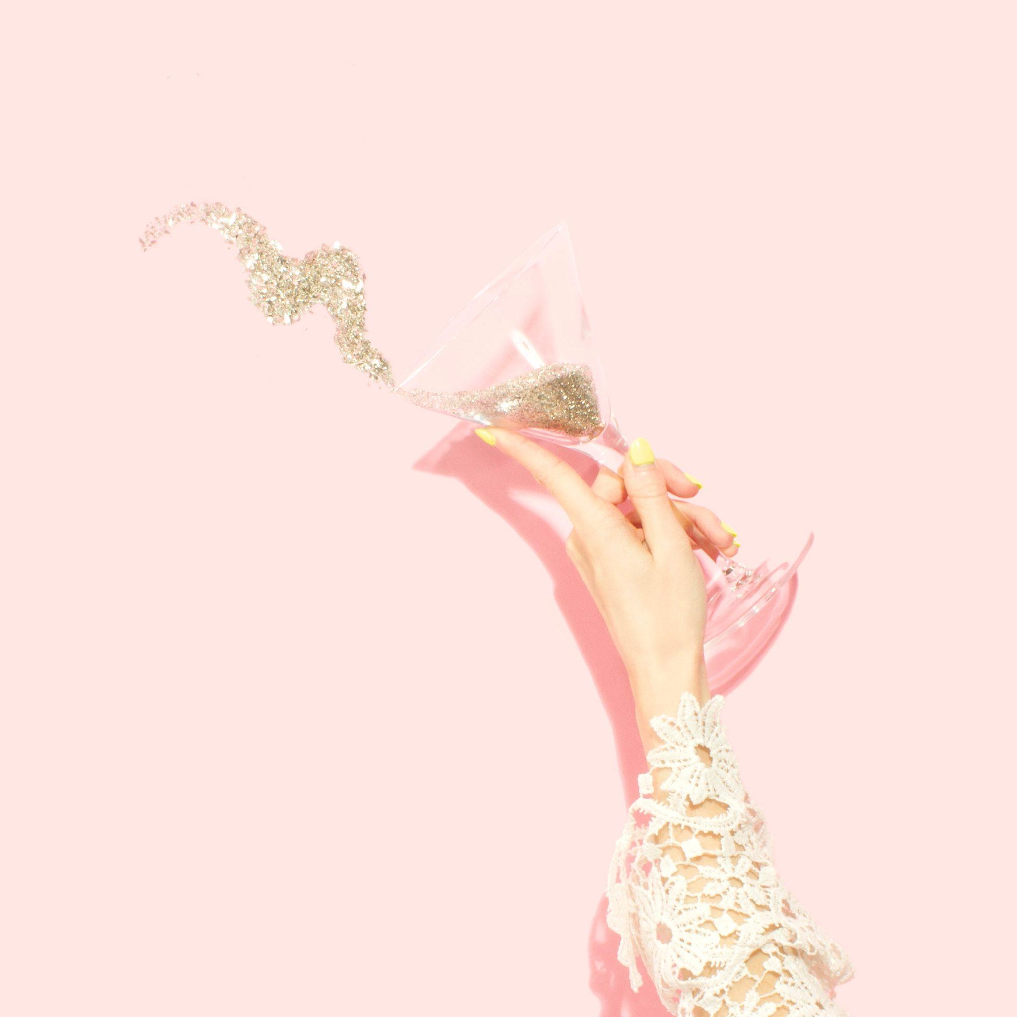 mano di donna che festeggia i suoi successi lanciando in aria un calice di brillantini - foto in CC tatianaberlaffa.com