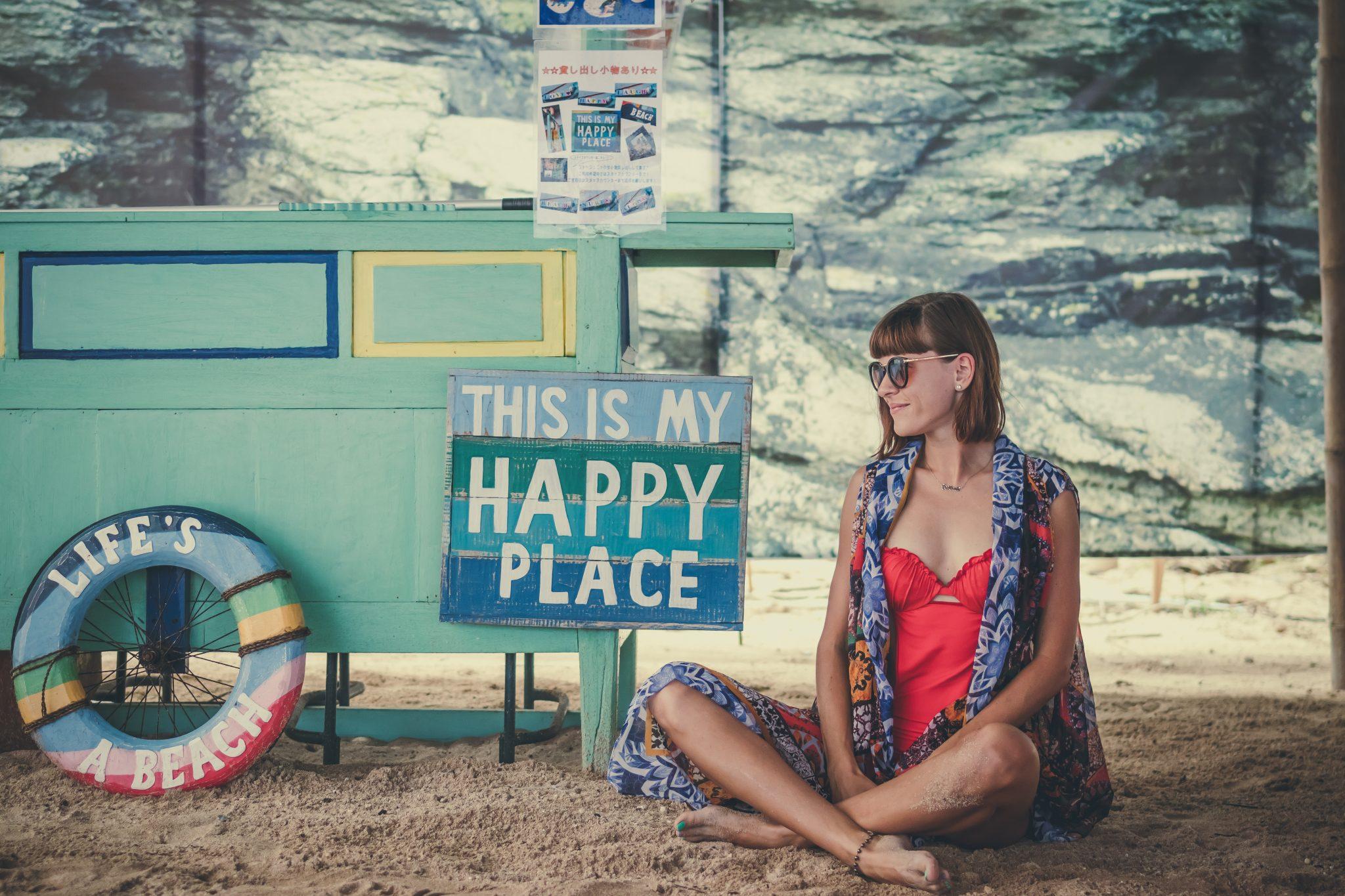 Ragazza felice seduta di fianco ad un cartello scritto in inglese 'Questo è il mio posto felice' - foto in CC pubblicata da tatianaberlaffa.com