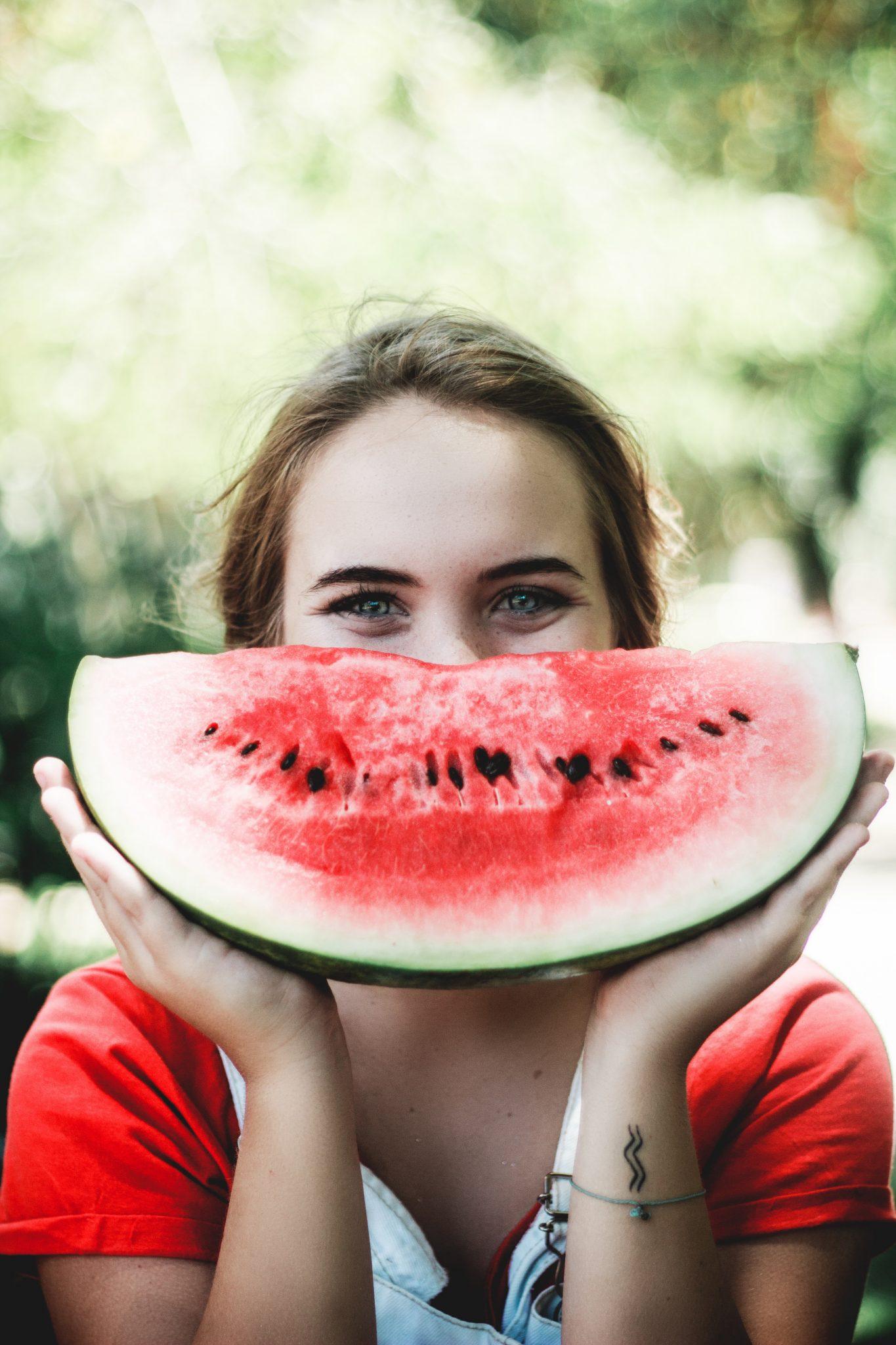 Donna che sorride con una fetta di anguria tra le mani. Ossitocina è un ormone che produce benessere e gioia. Foto in CC pubblicata da tatianaberlaffa.com