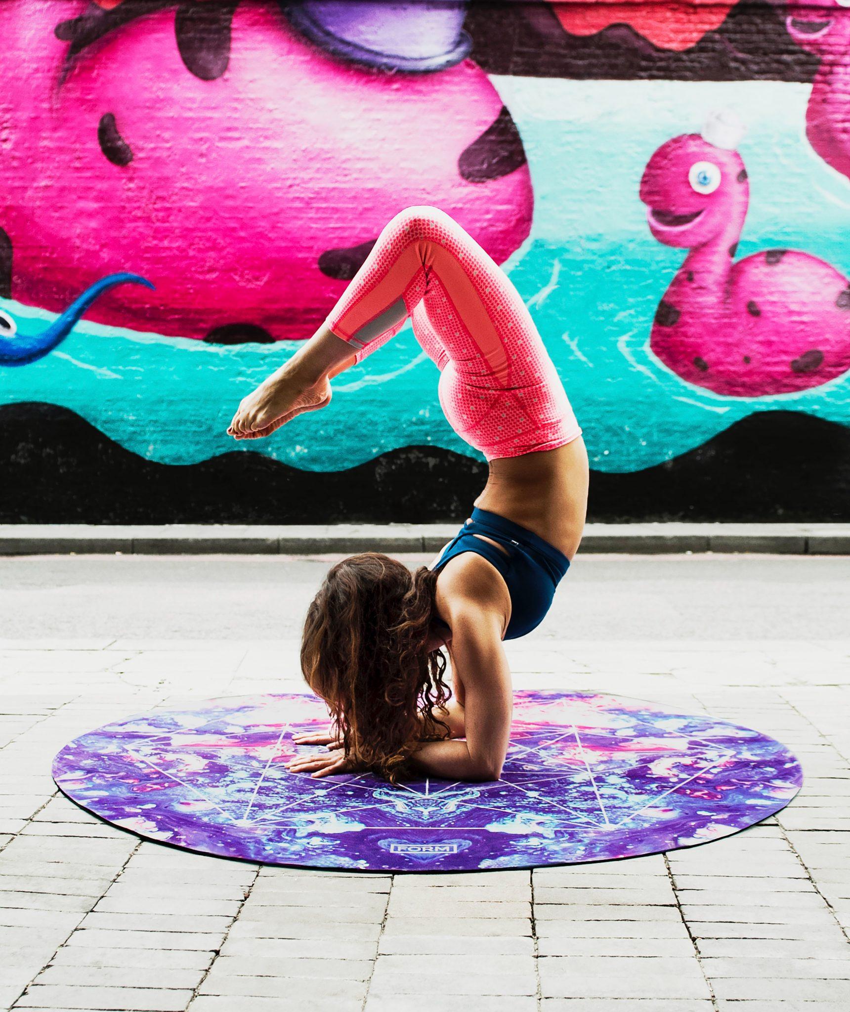 Donna che fa sport in posizione acrobatica su un tappetino da yoga - foto in CC tatianaberlaffa.com