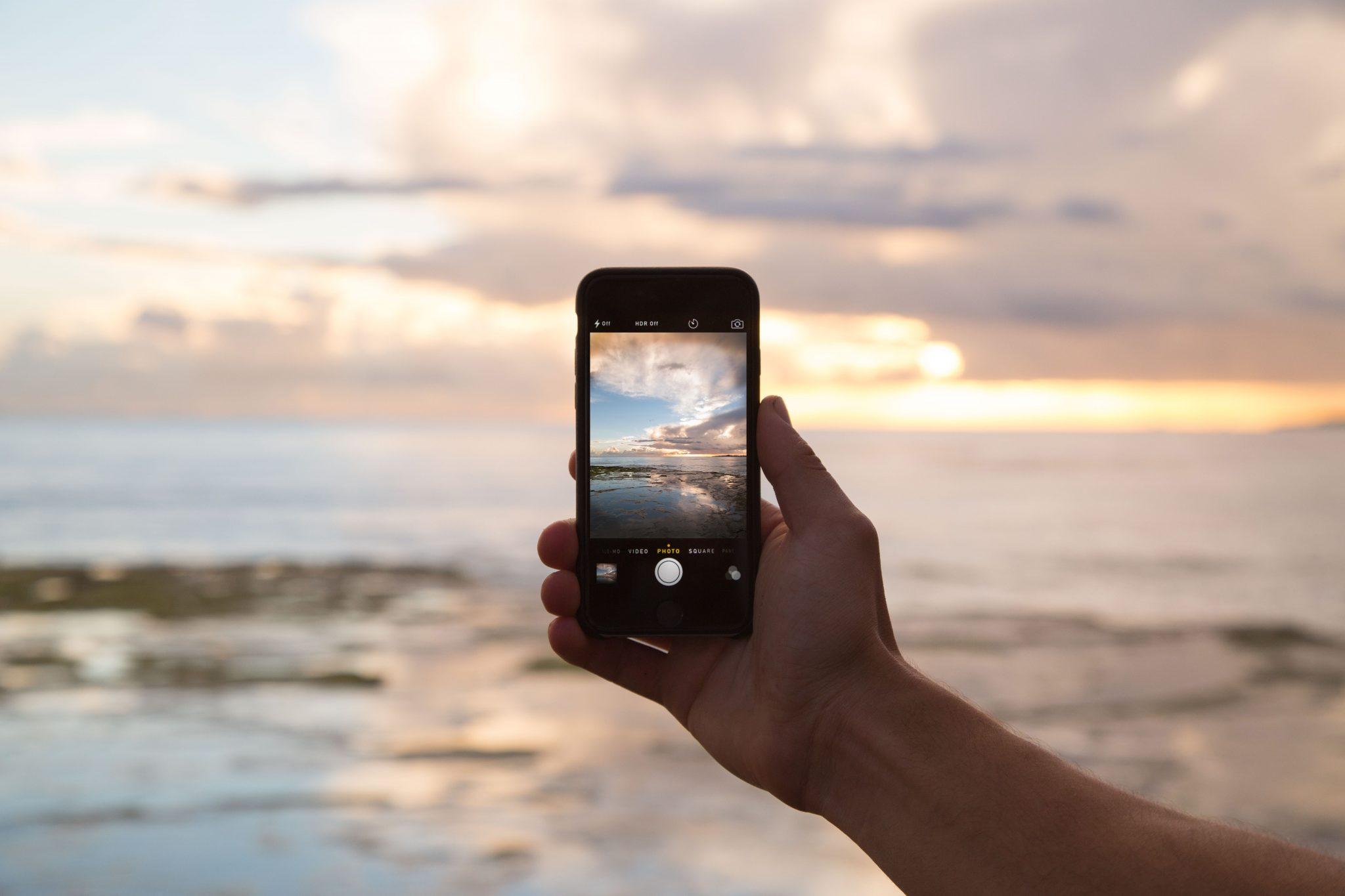 Mano di una persona che scatta fotografie di un tramonto al mare con lo Smartphone - foto in CC pubblicata da tatianaberlaffa.com