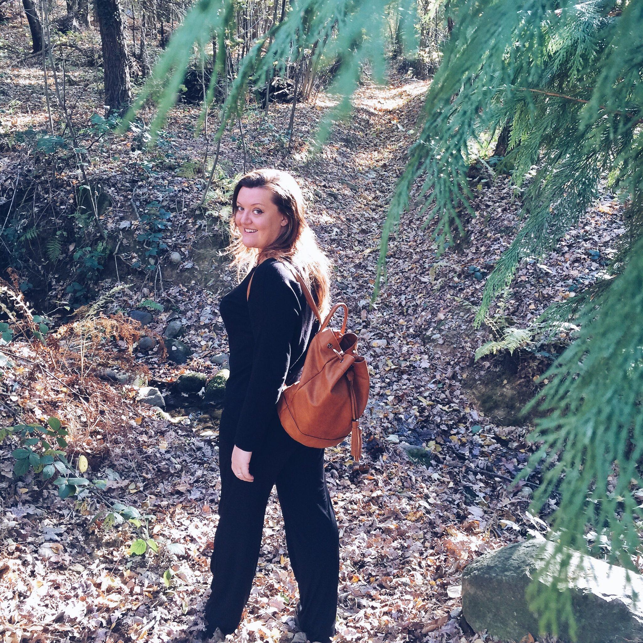 Donna che cammina nel bosco con zaino in spalla - tatianaberlaffa.com