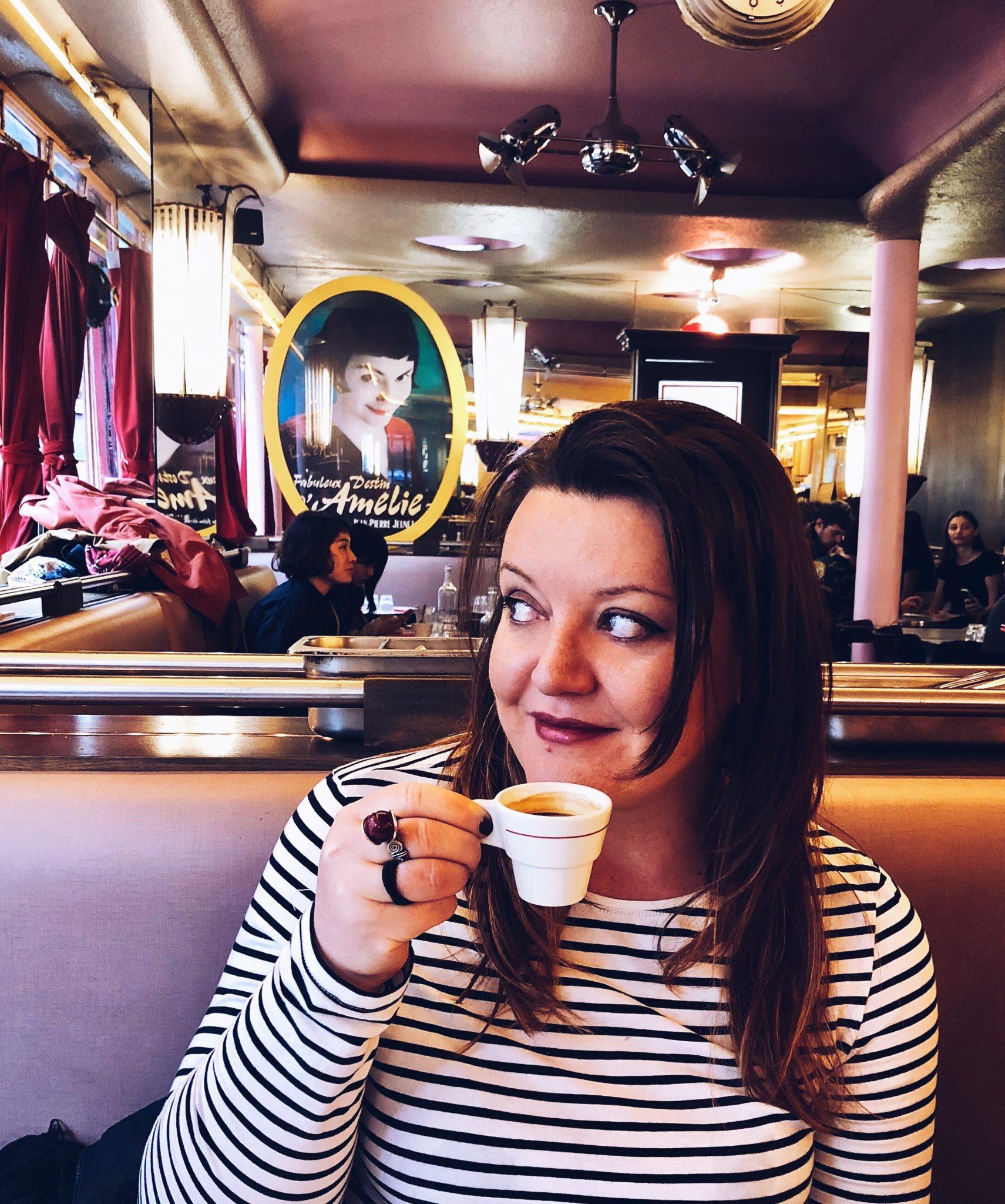 ragazza che sorseggia un caffè al Cafè des deux Moulins a Parigi con un manifesto del favoloso mondo di Amélie sullo sfondo - tatianaberlaffa.com