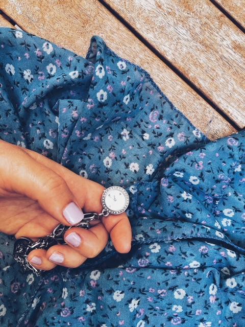 Equilibrio vita privata e lavoro: mano di donna che tiene orologio da polso su stoffa a fiori - foto di tatianaberlaffa.com