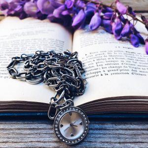 work balance: libro aperto con orologio da donna da polso e fiori viola di glicine - foto di tatianaberlaffa.com