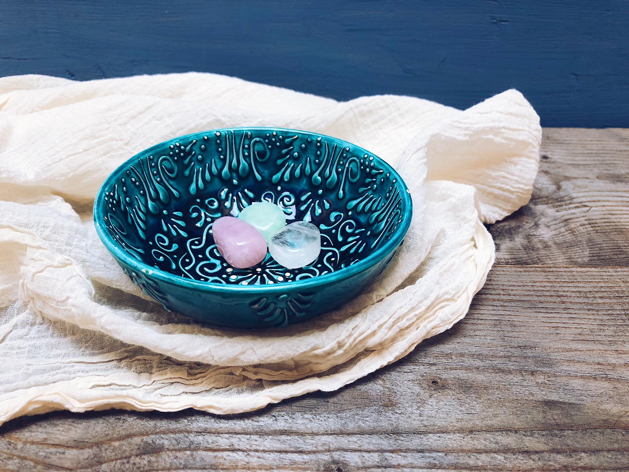 pietre in una scodella di ceramica blu su stoffa bianca e fondale di legno - tatianaberlaffa.com