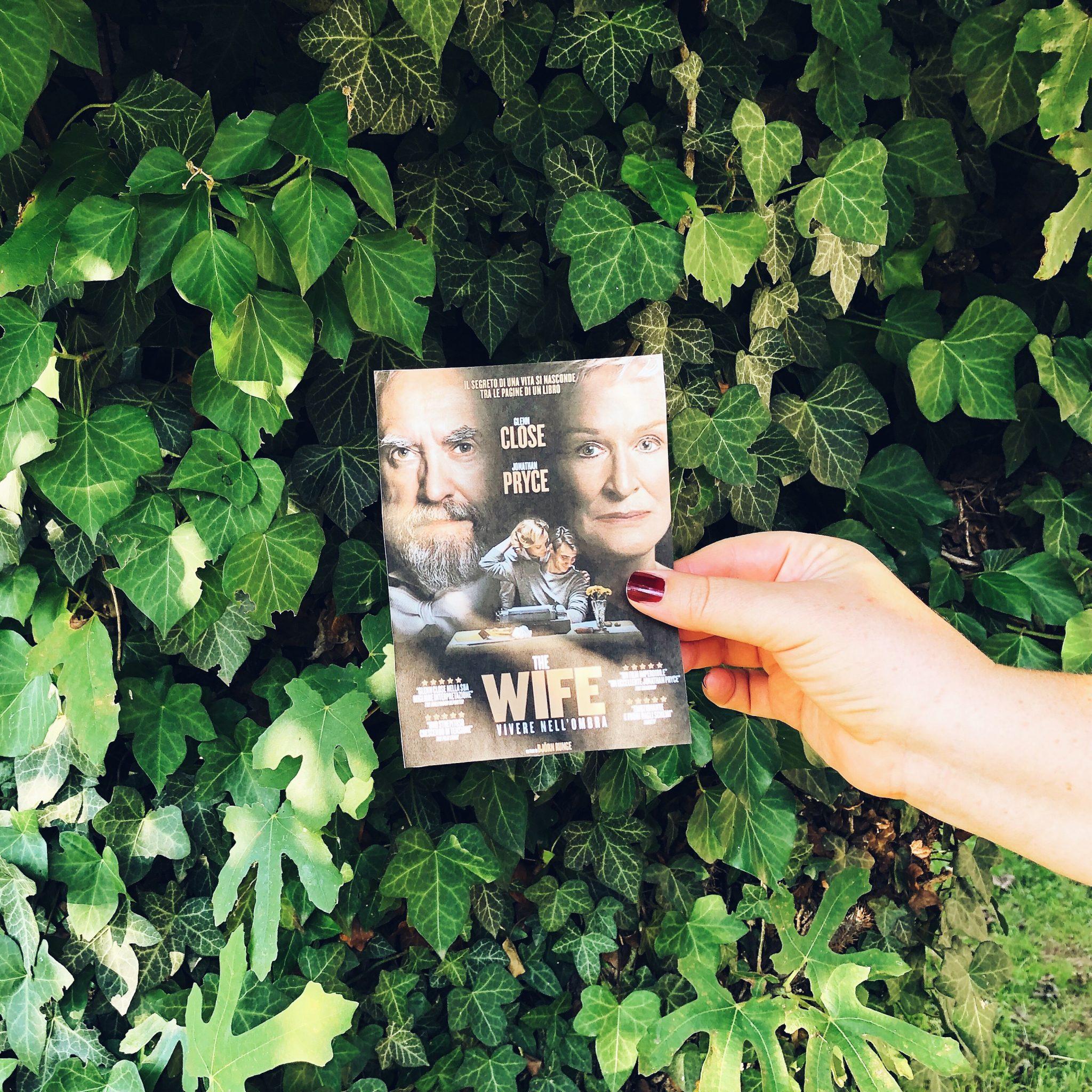 Mano che sorregge la Locandina del film The Wife su uno sfondo di foglie verdi - foto di tatianaberlaffa.com
