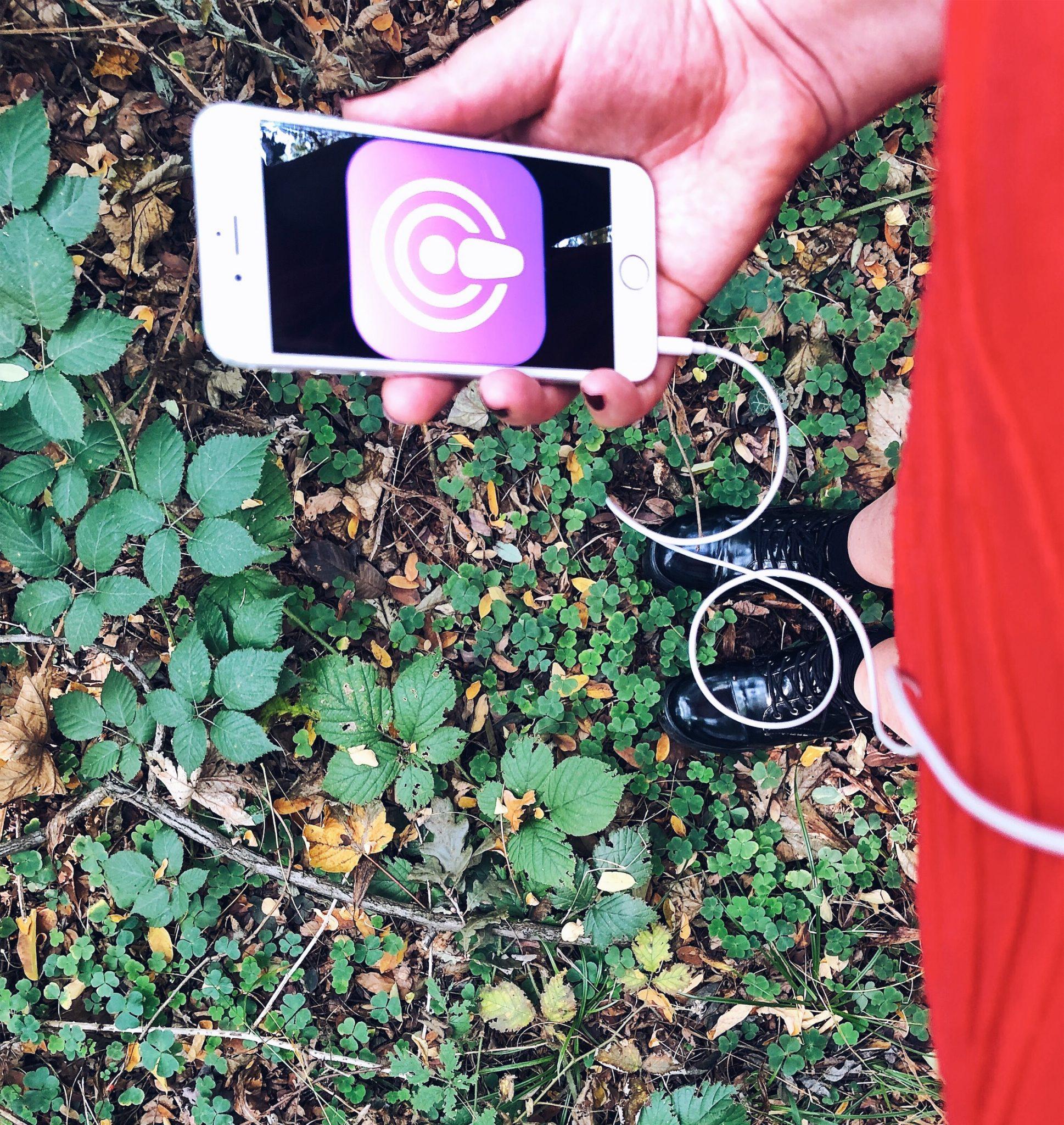 I 5 migliori podcast italiani di crescita personale - donna in un bosco con smartphone in mano e cuffie - tatianaberlaffa.com