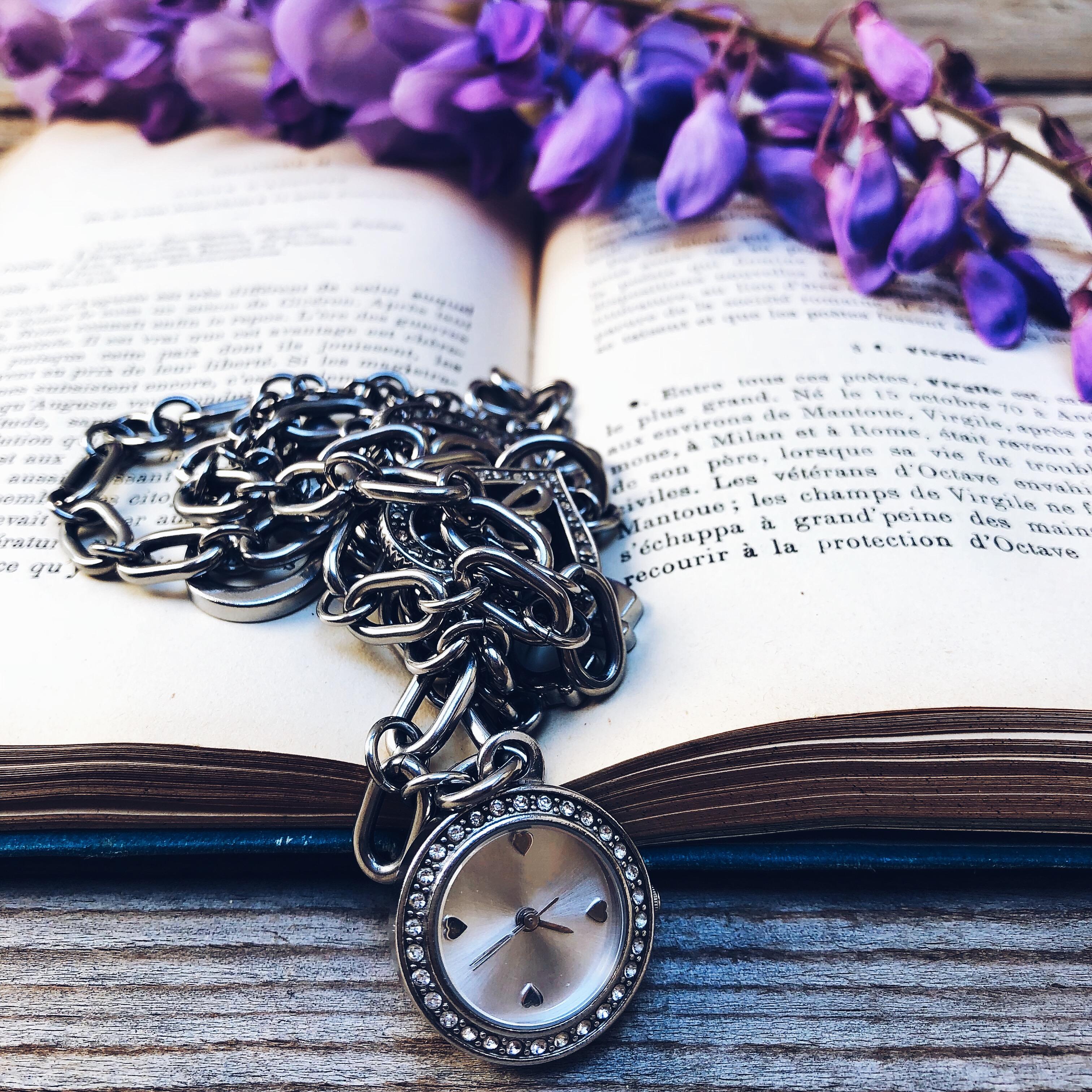 Orologio d'argento appoggiato su un libro con fiori di glicine - Servizi personalizzati di Comunicazione - tatianaberlaffa.com