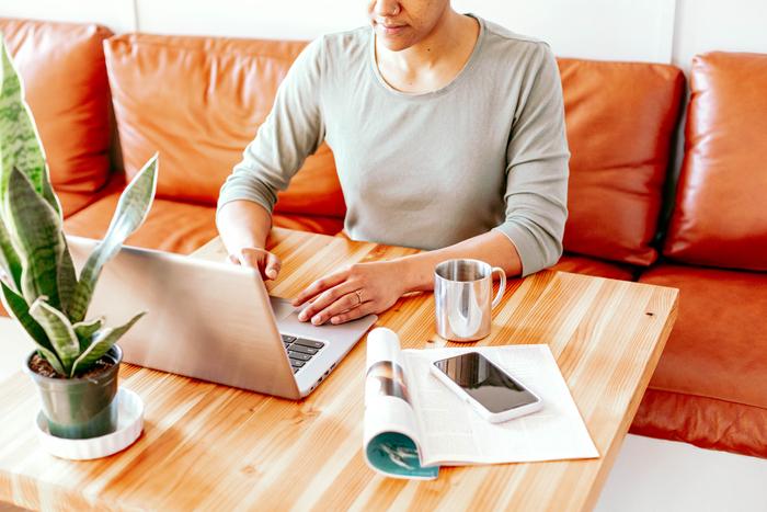 Donna al lavoro che scrive al computer in salotto utilizzando la tecnica del pomodoro per essere più produttiva